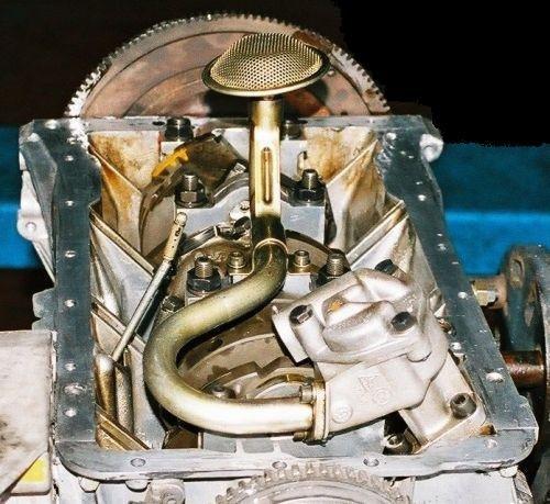 Zdjęcie przedstawiające pomę oleju w 12 zaworowej V6, widać smok, który za pośrednictwem rurki łączy się z mechanizmem pompy przykręconej na spód bloku, przy miejscu mocowania właśnie wychodzi wałek do zębatki przy kole pasowym